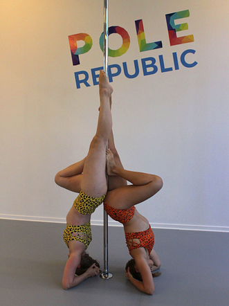 two girls doing headstand on a pole
